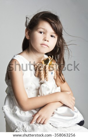 Adorable little girl cuddles and plays with her doll - stock photo