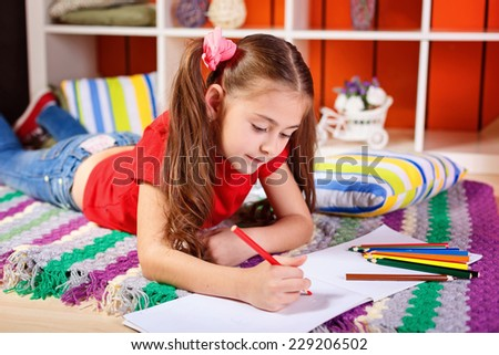 adorable little girl drawing with pencils at the children's room