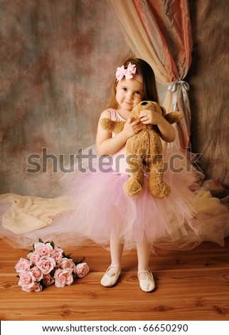Adorable little girl dressed as a ballerina in a tutu, hugging a teddy bear standing next to pink roses. - stock photo