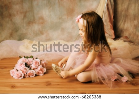 Adorable little girl dressed as a ballerina in a tutu, tying her ballet slippers. - stock photo