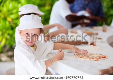 Adorable little girl dressed as a chef making pizza - stock photo