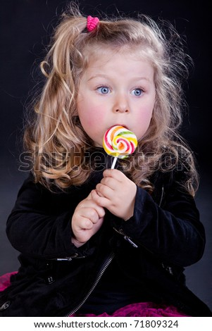 Adorable little girl eating big rainbow lollipop - stock photo