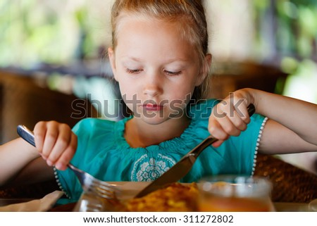 Adorable little girl eating breakfast in restaurant - stock photo