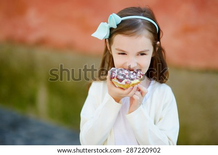 Adorable little girl eating fresh sweet strawberry cake outdoors on warm and sunny summer day in Italy - stock photo