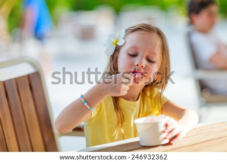 Adorable little girl eating ice cream - stock photo