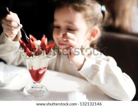 Adorable little girl eating ice cream at restaurant - stock photo