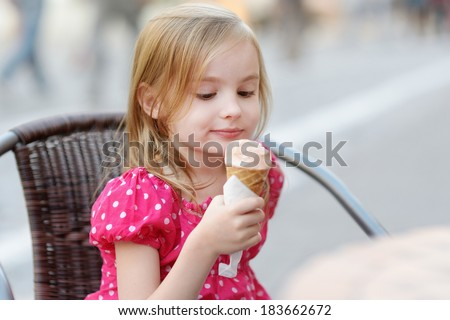 Adorable little girl eating ice-cream outdoors at summer - stock photo