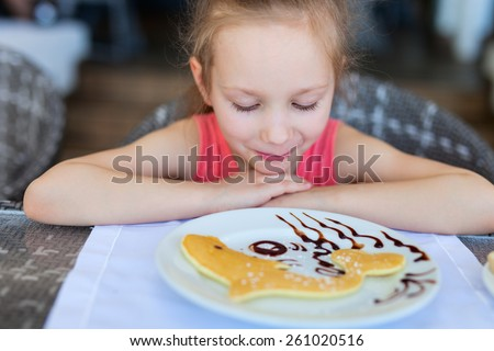 Adorable little girl eating pancake for a breakfast in restaurant - stock photo