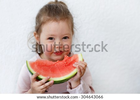 Adorable little girl eats a slice of watermelon indoors - stock photo