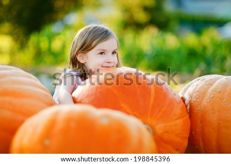 Adorable little girl embracing big pumpkin on a pumpkin patch - stock photo