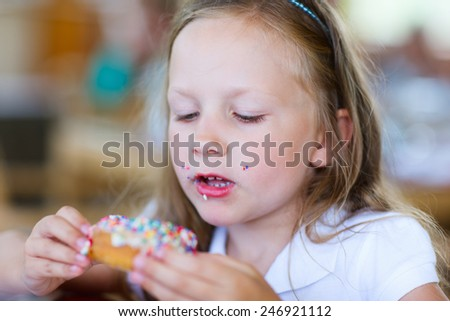 Adorable little girl enjoying eating donut at cafe - stock photo