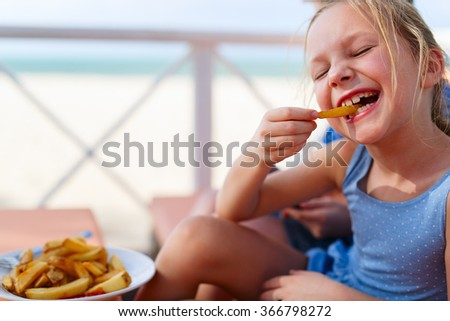 Adorable little girl enjoying eating french fries at outdoors restaurant on summer day