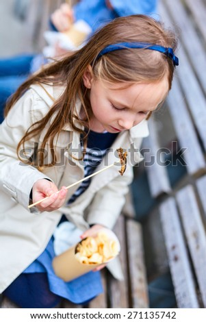 Adorable little girl enjoying eating take away food for lunch outdoors - stock photo
