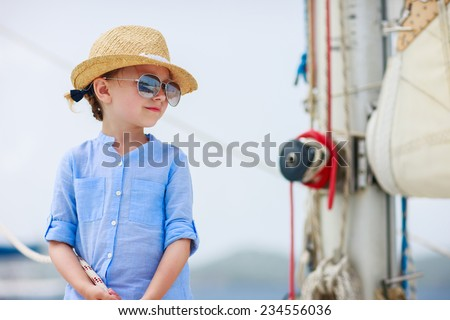 Adorable little girl enjoying sailing on a luxury catamaran or yacht - stock photo