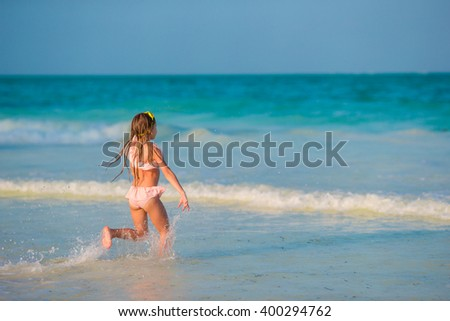 Adorable little girl have fun at beach - stock photo