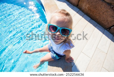 Adorable little girl have fun near pool outdoors - stock photo