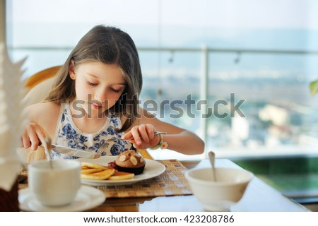 Adorable little girl having breakfast at  hotel restaurant - stock photo