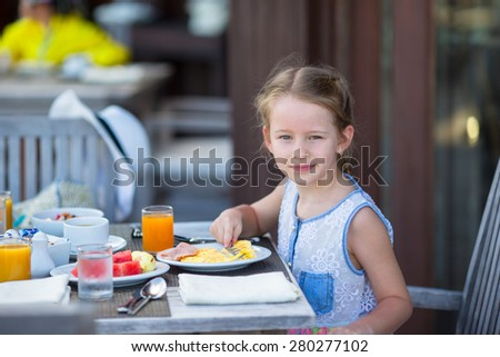 Adorable little girl having breakfast at outdoor cafe - stock photo
