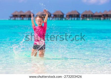 Adorable little girl having fun at th beach - stock photo