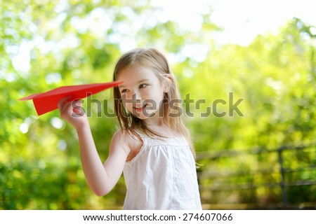 Adorable little girl holding a paper plane outdoors on sunny summer day - stock photo