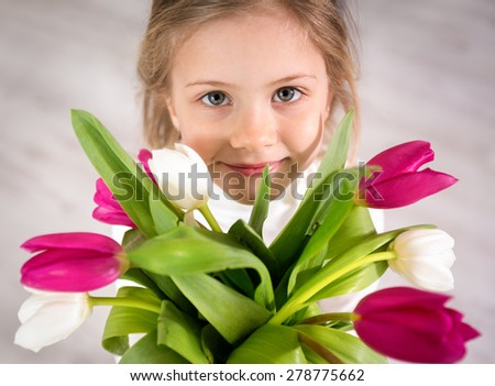 Adorable little girl holding bouquet of tulips, top view - stock photo