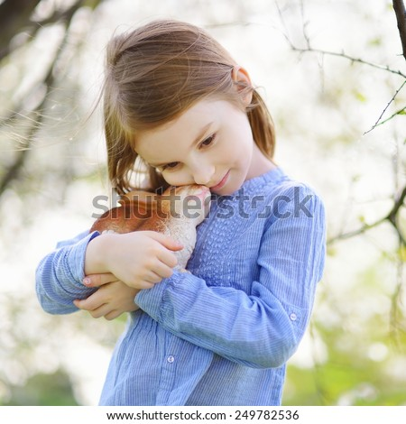 Adorable little girl holding easter bunny in blooming cherry garden on beautiful spring day - stock photo