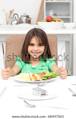 Adorable little girl holding forks to eat pasta and salad in the kitchen - stock photo