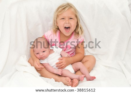 Adorable little girl holding her baby brother - stock photo