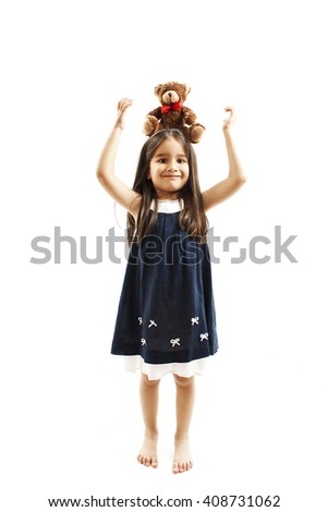 Adorable little girl holding teddy bear on head. Isolated on white background - stock photo