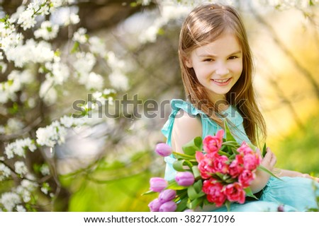 Adorable little girl holding tulips for her mother in blooming cherry garden on beautiful spring day - stock photo