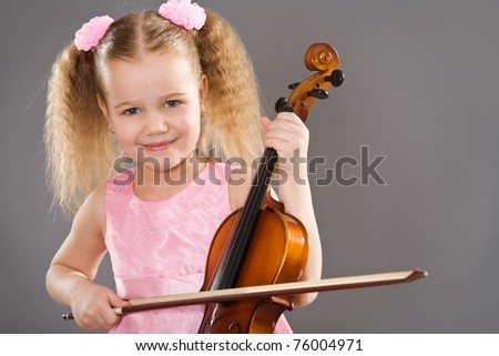 Adorable little girl holding violin - stock photo