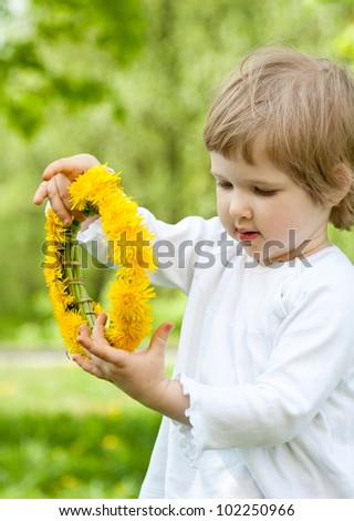 Adorable little girl holding yellow chaplet made of dandelions - stock photo