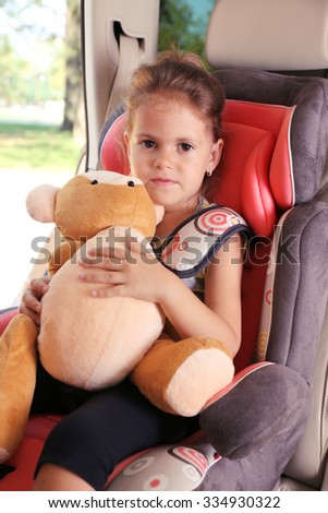 Adorable little girl holds bear in the car - stock photo