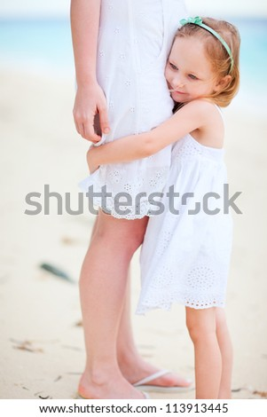 Adorable little girl hugs her mom at beach