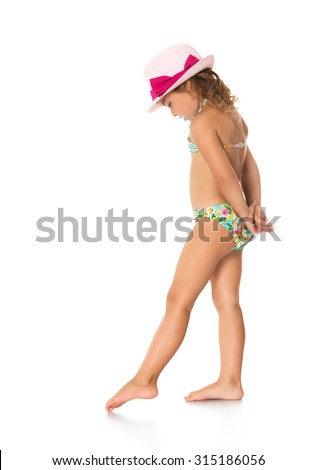 Adorable little girl in a bathing suit and a pink hat draws his foot on the sand. The girl turned sideways and about something much thought-Isolated on white background - stock photo