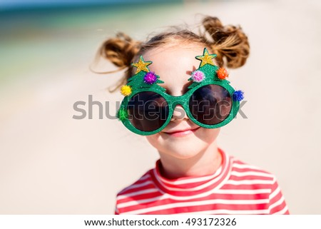 Adorable little girl in a funny Christmas glasses at tropical beach