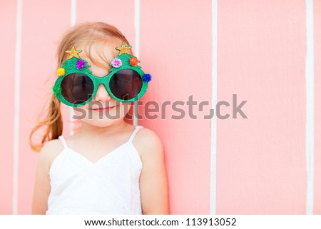 Adorable little girl in a funny Christmas glasses over colorful Caribbean house background