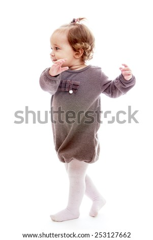 Adorable little girl in a gray dress.Isolated on white background. - stock photo