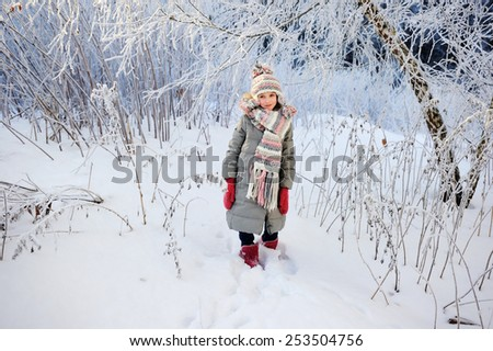 Adorable little girl,  in a knitted hat and gray down coat, playing  outdoors in a beautiful winter park - stock photo