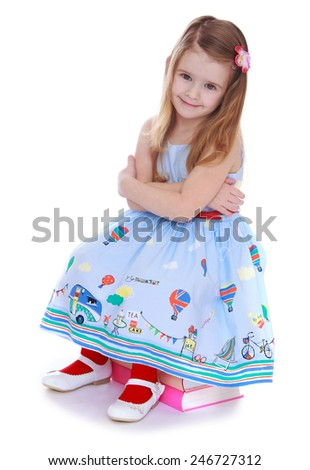 Adorable little girl in a long dress sitting on a pile of books.Isolated on white background - stock photo