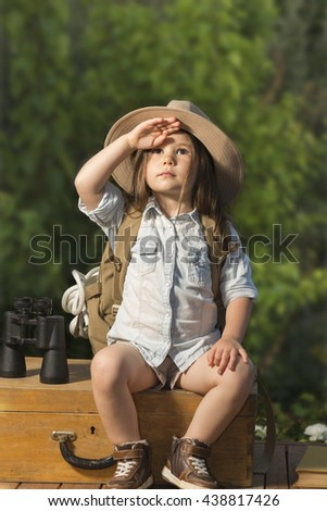 Adorable little girl in a safari hat and explorer clothes playing safari sitting on wooden suitcase outdoor. Children's play concept. Looking for the summer vacation - stock photo