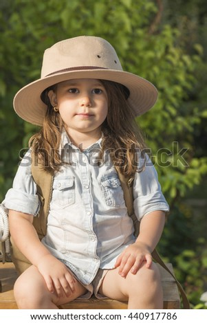Adorable little girl in a safari hat and explorer clothes playing safari sitting on wooden suitcase outdoor. Looking for the summer vacation. Children's play concept - stock photo