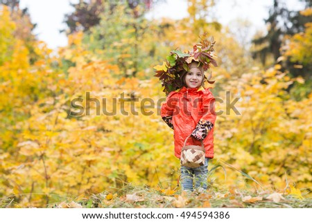 adorable little girl in a wreath from leaves in the beauty park