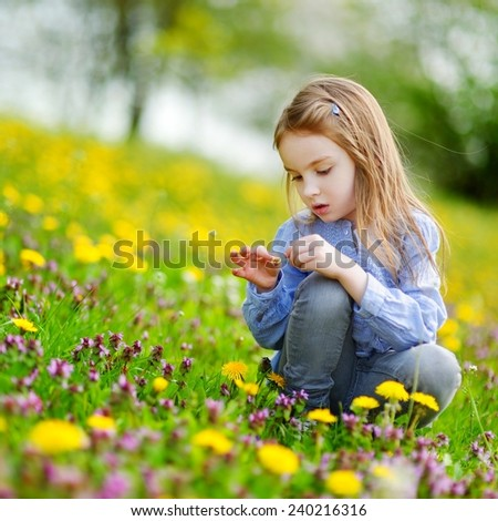 Adorable little girl in blooming dandelion flowers - stock photo