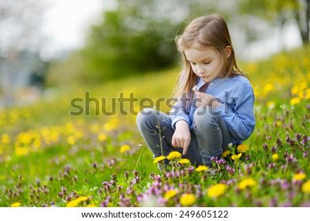 Adorable little girl in blooming dandelion flowers - stock photo