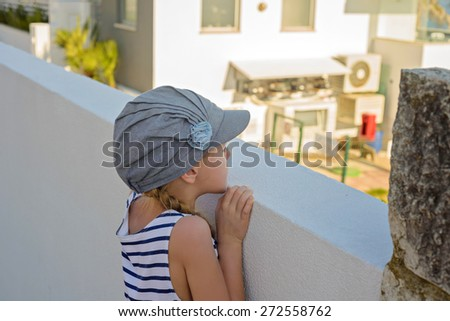 Adorable little girl in denim cap in the city watching thru wall - stock photo