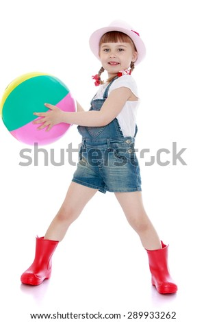 Adorable little girl in denim overalls holding a ball - isolated on white background - stock photo