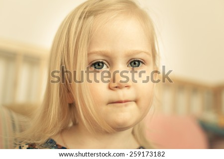 Adorable little girl in her room. Thoughtful, pensive face. - stock photo