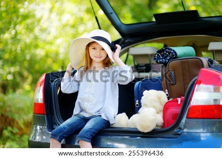 Adorable little girl in summer hat leaving for a car vacation with her parents - stock photo