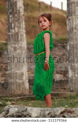 Adorable little girl in the emerald dress on a background of ancient sites of the ancient Greek city of Patikapey - stock photo